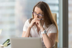 Image of pensive businesswoman seating in office. Portrait of pensive business woman seating at the table in office. Focused middle-aged woman in glasses resting Royalty Free Stock Images