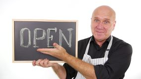 Image with a person smiling happy and showing open text written on a chalkboard.  stock footage