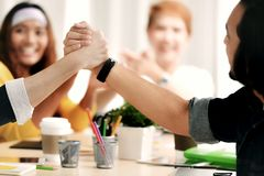 Image of 2 persons firmly holding hands in agreement. In meeting at office Royalty Free Stock Photos