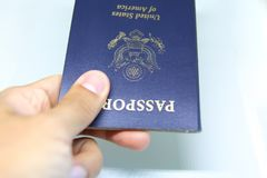 Image of a persons hand holding a passport Stock Photo