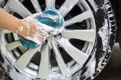 Man hands hold with blue sponge washing car. royalty free stock photo