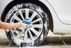 Man hands hold with blue sponge washing car. royalty free stock image