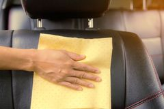 This image is a picture of wiping the car with a yellow microfiber cloth by hand. Stock Photography