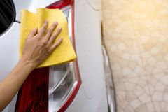 This image is a picture of wiping the car with a yellow microfiber cloth by hands. Car wash concept Stock Photos
