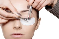 The pincers are being applied to the female face making the fake eyelashes. Horizontal view royalty free stock photography