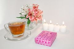 Image of a pink luxury gift box with a bouquet of beautiful Alstroemeria flowers, a romantic candle and cup of tea, a festive stil royalty free stock image