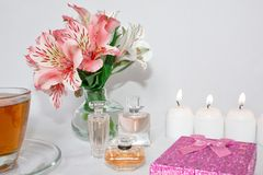 Image of a pink luxury gift box with a bouquet of beautiful Alstroemeria flowers, a romantic candle and perfume. A festive still life, lit candles. Greeting royalty free stock images