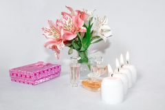 Image of a pink luxury gift box with a bouquet of beautiful Alstroemeria flowers, a romantic candle and perfume. A festive still life, lit candles. Greeting stock images