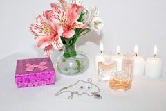 Image of a pink luxury gift box with a bouquet of beautiful Alstroemeria flowers, a romantic candle and perfume. A festive still life, lit candles. Greeting stock image