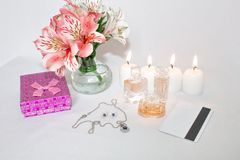 Image of a pink luxury gift box with a bouquet of beautiful Alstroemeria flowers, romantic candles, perfume, jewelry and a credit. Card. Dressing table with stock photos