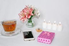 Image of a pink luxury gift box with a bouquet of beautiful Alstroemeria flowers, romantic candles, perfumery, tea cups. And a cell phone. Dressing table with royalty free stock images