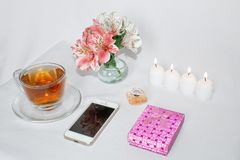 Image of a pink luxury gift box with a bouquet of beautiful Alstroemeria flowers, romantic candles, perfumery, tea cups. And a cell phone. Dressing table with royalty free stock photography