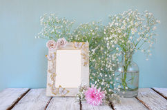 Image of pink and white flowers and antique frame on wooden table. template, ready to put photography Royalty Free Stock Photo