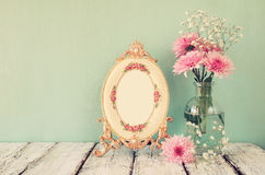 Image of pink and white flowers and antique frame on wooden table. vintage filtered Stock Photo