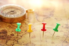 Image of pins attached to map, showing location or travel destination next to vintage compass. selective focus. stock photo