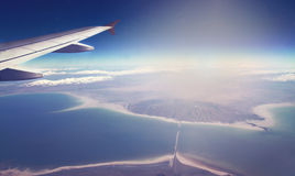 Image of plane and wing with sea, mountains, and coastline. Horizont line and sunrise. Royalty Free Stock Photos