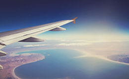 Image of plane and wing with sea, mountains, and coastline. Horizont line and sunrise. Stock Photo