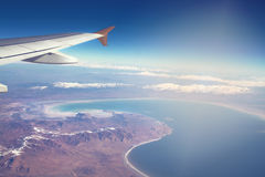 Image of plane and wing with sea, mountains, and coastline. Horizont line and sunrise. Stock Image