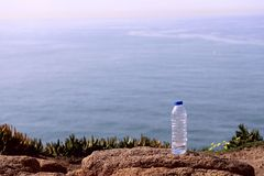 The image of a plastic bottle on a mountain cliff against the background of the ocean. stock images