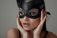 Brunette girl in a cat mask stock photography