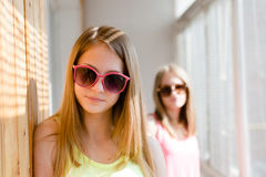 Image of 2 playful in sun glasses best girl friends or sisters beautiful blond young women having fun posing happy smiling. Portrait of best girl friends or Royalty Free Stock Images
