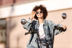Image of pleased curly woman in sunglasses sitting on motorbike Royalty Free Stock Photos