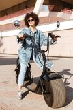 Image of pleased curly woman in sunglasses sitting on motorbike Stock Photo