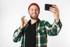 Image of pleased guy wearing hat and plaid shirt taking selfie photo on cell phone, while standing isolated over white background. Image of pleased guy wearing royalty free stock photo