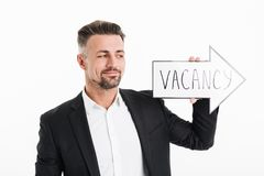 Image of pleased man wearing black jacket looking on speech arro. W pointer with word vacancy holding in hand isolated over white background Stock Image