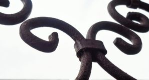 4 Curls Wrought Iron Against Grey Sky. This is an image of a portion of an antique wrought iron garden decoration. It could represent a feeling of history royalty free stock photo