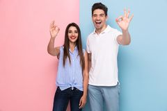 Image of positive couple in casual t-shirts smiling and gesturing ok sign, isolated over colorful background. Image of positive couple in casual t-shirts smiling royalty free stock photography