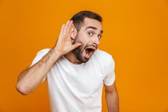 Image of positive man 30s trying to hear something while keeping hand at his ear,  over yellow background. Image of positive man 30s trying to hear something stock image