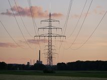 Image of power line during sunset with power plant stock photography