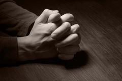 Image of praying hands. In dark Stock Photos