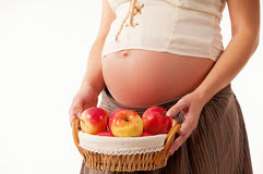 The image of a pregnant woman. The image of a pregnant woman with a basket of apples Royalty Free Stock Photos