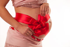 The image of a pregnant woman. We are waiting for a gift. Bow on his tummy Stock Images