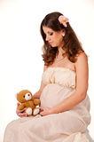 The image of a pregnant woman sitting with a teddy. Bear in her arms Royalty Free Stock Photos