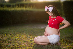 Image of pregnant woman touching her belly with hands Stock Image