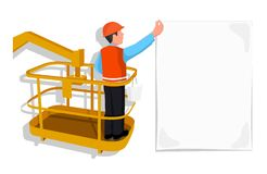 Worker standing in an assembly cradle glues a paper banner. Stock Image