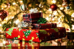 Image of presents and gifts. Different present boxes under Christmas tree in holiday eve, Christmastime celebration, home decorated with festive shiny balls stock photo