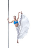 Image of pretty dancer posing in split on pole Royalty Free Stock Images