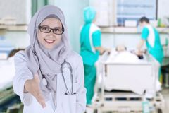 Muslim doctor offering handshake in the hospital. Image of pretty Muslim female doctor offering a handshake while standing in the patient room royalty free stock photo