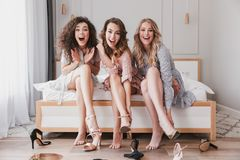 Image of pretty stylish women 20s wearing dresses trying on summer stilettos or high heels, during bridal shower in posh apartment. Image of pretty stylish women royalty free stock images
