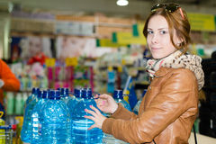 Image of pretty woman buying a bottle of water looking at camera smiling in supermarket Stock Photo