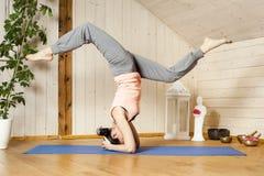 Yoga woman. An image of a pretty woman doing yoga at home - Eka Pada Shirshasana Royalty Free Stock Photo