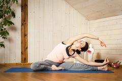 Yoga woman. An image of a pretty woman doing yoga at home - Parivrtta Janu Shirshasana Royalty Free Stock Photography