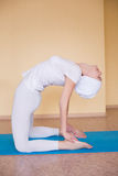 An image of a pretty woman doing yoga at home - Ushtrasana Royalty Free Stock Photos