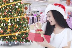 Excited woman opening her Christmas gift. Image of pretty woman looks excited while opening her Christmas gift while standing in the shopping center Stock Image