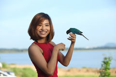 Image of  pretty woman pose and smile with green bird Royalty Free Stock Photo