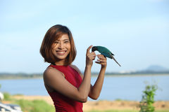 Image of pretty woman pose and smile with green bird Stock Photos
